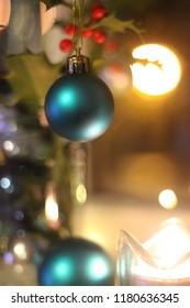Teal blue Christmas decoration baubles hanging from holly leaves with bokeh background