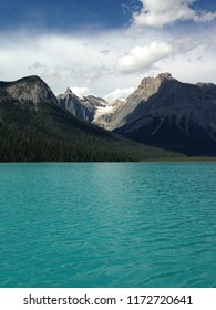 Teal blue glacial fed lake with mountain range in the background