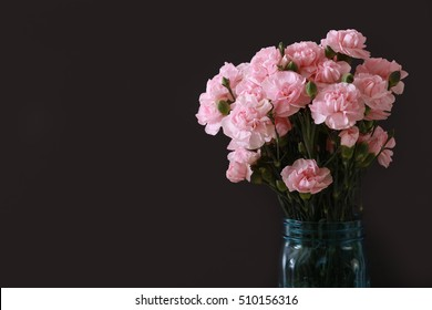A teal blue jar vase filled with miniature pink carnations and a dark black background with plenty of text area copy space..