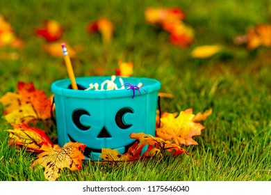 teal bucket with non-food treats outside. trick or treating. the concept of health for children in the Halloween season. Copy space for your text
