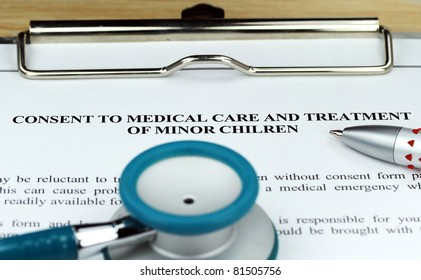 A Teal colored stethoscope on a metal  clipboard along with a pen  for you to sign a medical consent form for a minor.