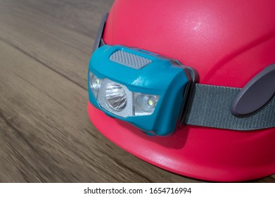 Teal led headlamp turned off strapped to a pink climbing helmet on a wooden table