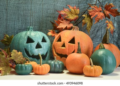 Teal and orange pumpkins in a Halloween still life with maple leaf boughs and black netting indicating that both allergy safe non food treats as well as candies are available to trick and treaters.