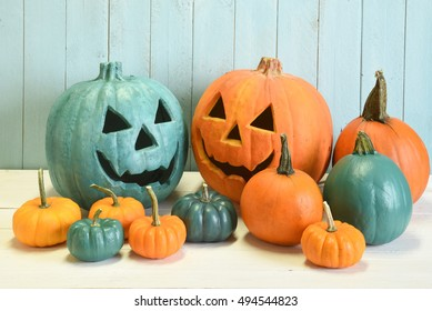 Teal and orange pumpkins in a Halloween still life indicating that both allergy safe non food treats as well as candies are available to trick and treaters.  Indoor studio shot on a aqua background