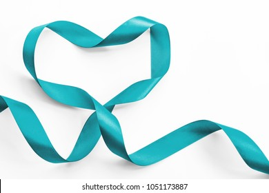 Teal ribbon awareness in heart shape isolated on white (clipping path) symbolic bow color for Ovarian Cancer, Polycystic Ovary Syndrome (PCOS) disease, Post Traumatic Stress Disorder (PTSD)