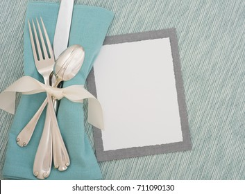 Teal Table Place Setting with Silverware, Cloth Napkin and Textured Turquoise Matt with a Menu Card with room or space for copy, text, or words.  A horizontal with flay lay, top overhead view.