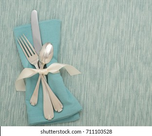 Teal Table Place Setting with Silverware, Turquoise Cloth Napkin on a Cyan, Textured Tablecloth or Mat with room or space for copy, test or words. A horizontal with flay lay, overhead above view.