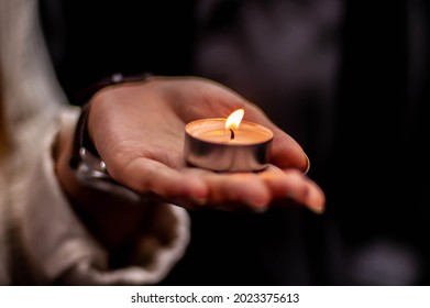 Tealight being held in the palm of a hand at a vigil