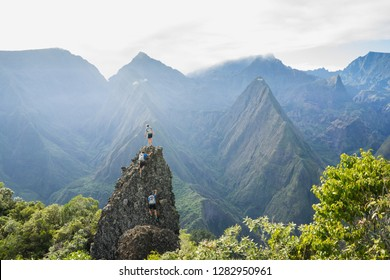 A team of 3 adventure racers climbing up a steep rocky pinnacle in the dense green jungle of Reunion Island