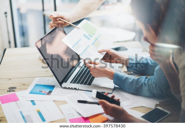 Team account manager project work.Photo business managers working with new startup in modern loft.Analyze reports,plans. Notebook on wood table, papers, documents, statistics. Horizontal, blurred