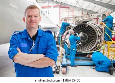 Team Of Aero Engineers Working On Aircraft In Hangar