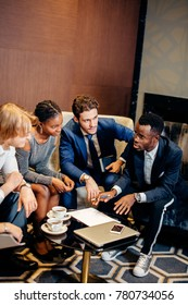 team of african and caucasian entrepreneurs meeting in office discussing business plan