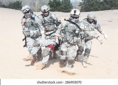 Team of airborne infantry paratroopers saving life of injured brother in arms dragging carrying him on desert sand. No man left behind