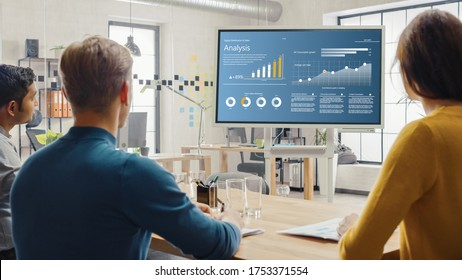Team of Analytics, Economists, Young Businesspeople Hold Meeting Presentation use Shows Digital Interactive Whiteboard with Growth Analysis, Charts, Statistics and Data. People Work in Creative Office - Shutterstock ID 1753371554