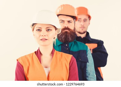 Team of architects, builders with calm faces, isolated white background. Woman and men in hard hats stand close as team. Builder, engineer, labourer, repairman as friendly team. Collective concept.