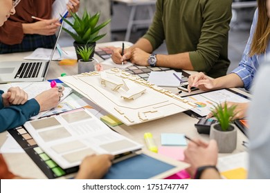 Team of architects and engineers working on urban building model scale. Hand of colleagues working on a house project. Close up of people hand working around prototype of a shopping center site.