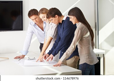 Team of architects working together on building plan in an office