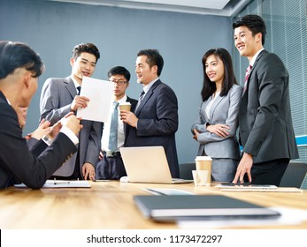 a team of asian business executives men and women working together in office.