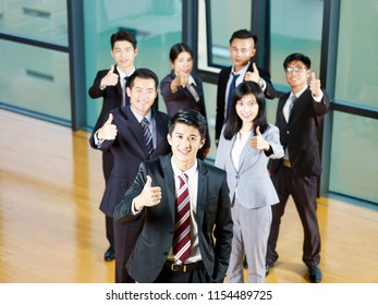 team of asian business people showing thumb-up sign.