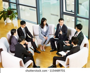 team of asian business people sitting in a circle meeting in office.