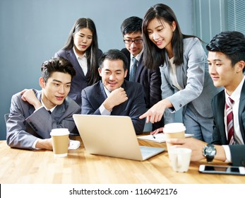 team of asian corporate people reviewing business result using laptop computer in office