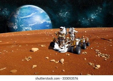 A team of astronauts explore a barren moon on a rover. The moon's water-covered parent planet rises over the horizon. -  Elements of this image furnished by NASA