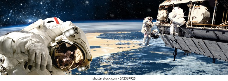 A team of astronauts perform work on a space station while orbiting a large, Earth-like planet. The stars of the galactic core radiate in the background. Elements of this Image Furnished by NASA.