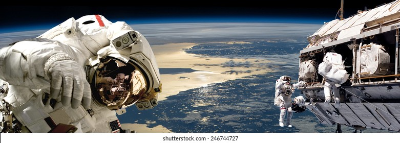 A team of astronauts performing work on a space station while orbiting over Earth. The sun reflects off the surrounding waters.  Elements of this Image Furnished by NASA.