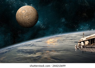 A team of astronauts work on a space station in orbit. An Earth-like planet sees the glow of its sun while a heavily cratered moon rises in the background. Elements of this Image Furnished by NASA.