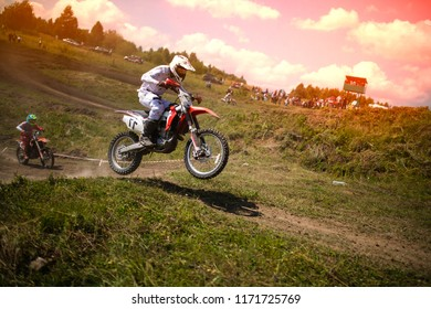 The team of athletes on mountain bikes starts, smoke and dust fly from under the wheels over rough terrain. The concept of active recreation motocross. soar into the sky. beautiful clouds