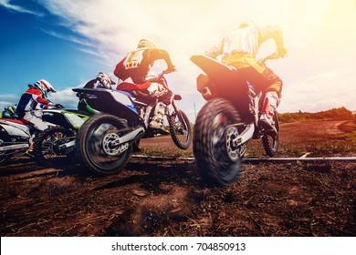 Team athletes on mountain motorcycles on motocross. Sun of light