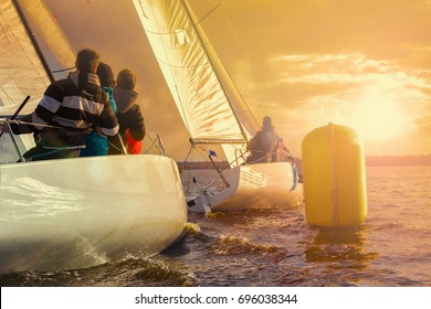 Team athletes participating in the sailing competition - match race.Two sailing yachts round the buoy. Sailboat at sunset. Recreational Water Sports, Extreme Sport Action. Healthy Active Lifestyle.