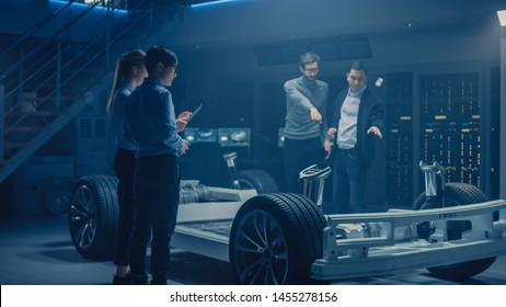 Team of Automobile Design Engineers in Automotive Innovation Facility Working on Electric Car Platform Chassis Prototype that Includes Wheels, Suspension, Hybrid Engine and Battery