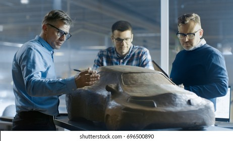Team of Automotive Design Engineers Discusses New Prototype Model Made of Plasticine Clay. They Work in a Large Car Factory.