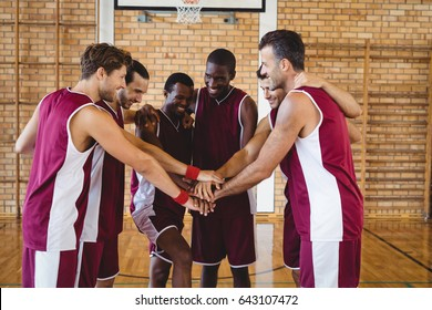 Team of basketball players stacking hands in the court