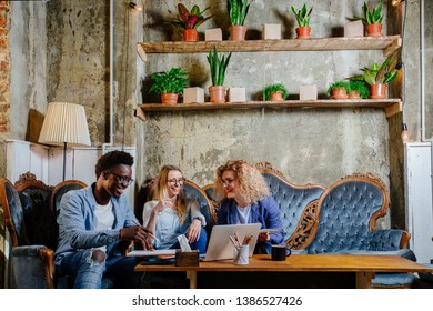 Team of black man and two blond women freelancer meeting for working solution in modern home office interior. Joint project real people models concept.