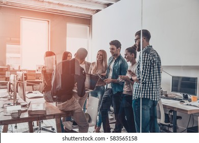 Team brainstorming.  Group of young modern people in smart casual wear having a meeting while standing behind the glass wall in the creative office