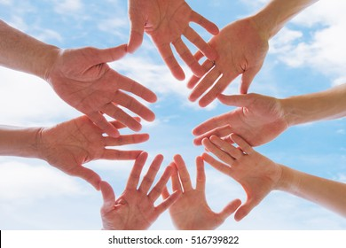 team or brotherhood concept, group of people putting hands together against blue sky