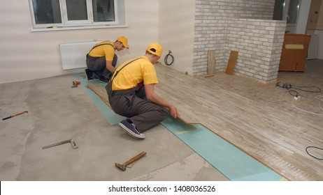 Team of builders make renovation of apartment. Construction workers laying floor board.