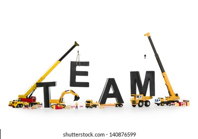 Team building concept: Black alphabetic letters forming the word team being established by group of construction machines, isolated on white background.