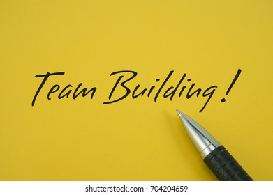 Team Building! note with pen on yellow background