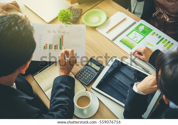 Team of business consulting, analysis of business plans. For profit and stability of business sustainability.Focus on hand Business man holding pen.