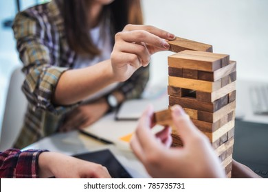 Team business hand's Plan and strategy in business, risk to make buiness growth with jenga wooden blocks.