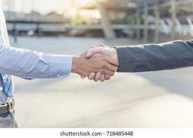 Team Business Partners shaking hands together to Greeting Start up new project. Corporate Teamwork Partnership outside office modern city as background. Businessman with Hands together.