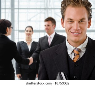 Team of business people, businessman in front, handsake in background.