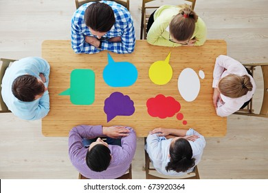 Team of business people in casual clothes sitting around the table with paper dialog boxes, discussing opinion concept