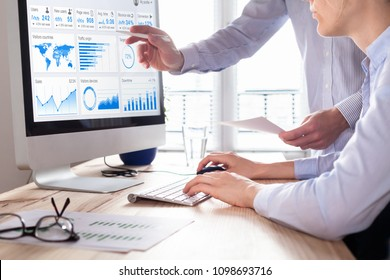 Team of business people discussing digital marketing metrics report and return on investment strategy for advertisement campaign, data analytics dashboard on computer screen in office