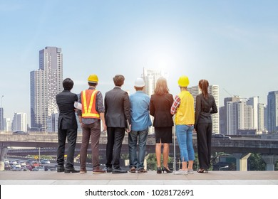 Team business people with engineer professional rear standing on skyscraper downtown with traffic jam in bangkok background