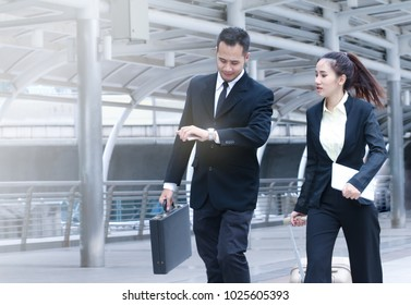 Team business people of a man and a woman hasten fast walking or hurriedly for urgent meeting and he looking his watch and time serious with team on rush hours in the morning