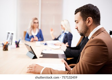 Team of business people at meeting in the conference room. They are discussing new projects. Two successful business women and two businessmen at the desk.